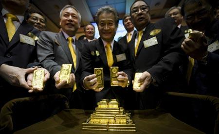 Aranyrudakat tartó bankárok Hongkongban. Forrás: Photo/Xinhua, Conclude Zrt.