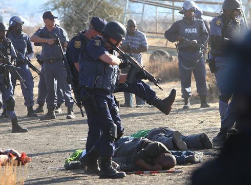 Dél-afrikai rendőrök az általuk lelőtt tüntetők felett. Forrás: timeslive.co.za, Conclude Zrt.
