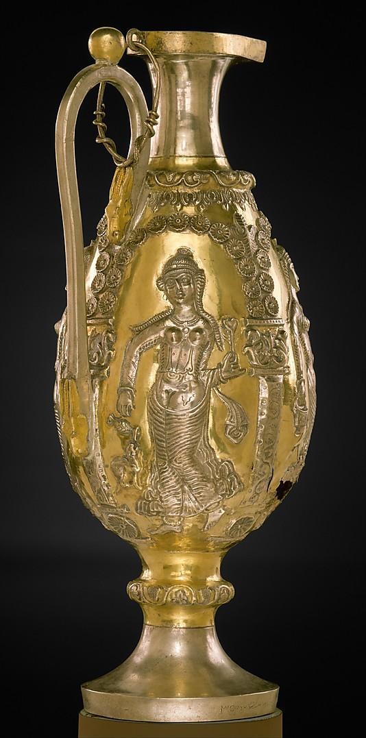 A késő újperzsiai ezüst tárgyakat, különösen az üvegeket és vizeskancsókat gyakran díszítették ünnepi tárgyakat tartó női alakokkal. Ezen az ezüst, aranyozott kancsón négy táncoló női alak is szerepel. Forrás: The Metropolitan Museum of Art, Conclude Zrt.